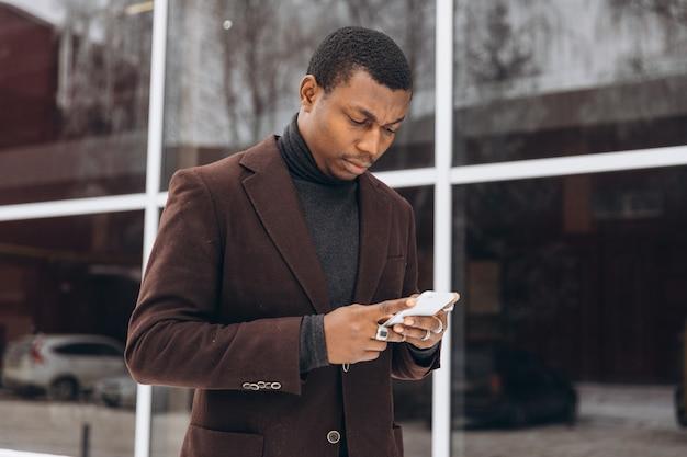 Afrikaner - porträt des hübschen afrikanischen - amerikanischen geschäftsmannes unter verwendung des smartphone.
