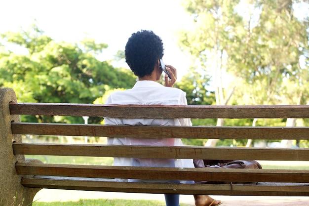 Afrikanerin, die auf einer parkbank unter verwendung des handys sitzt