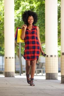 Afrikanerin, die mit einkaufstaschen und handy geht