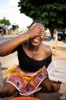 Afrikanerin gießt wasser in einen empfänger im freien