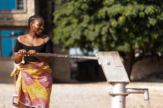 Afrikanerin gießt wasser in einen empfänger