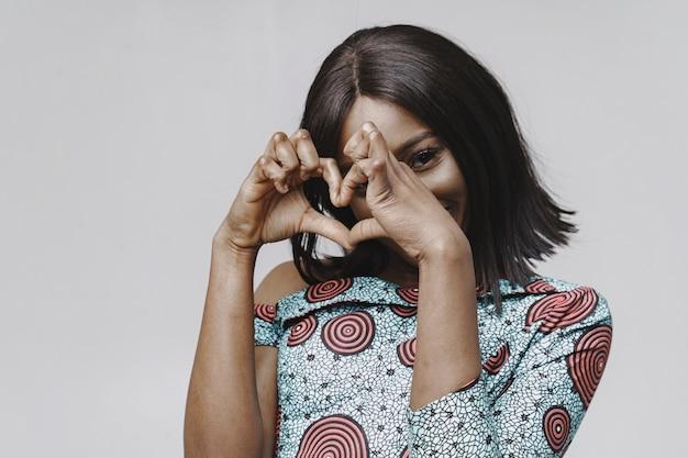 Afrikanerin in einem studio. weiße wand. frau in einem blauen kleid.