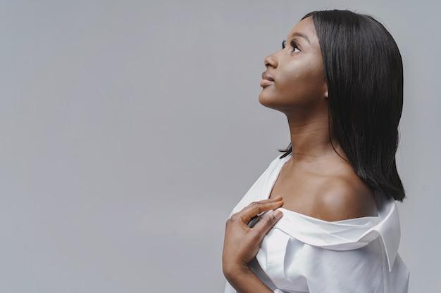 Afrikanerin in einem studio. weiße wand. frau in einem weißen hemd.