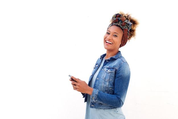 Afrikanerin mit dem intelligenten telefon, das gegen weißen hintergrund und lachen steht