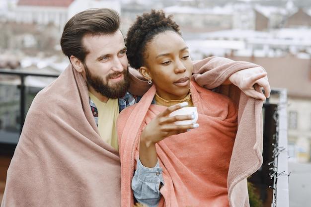 Afrikanerin mit ehemann. mann und mädchen in einem plaid. liebhaber trinken kaffee auf dem balkon.