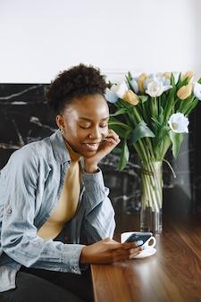 Afrikanerin mit telefon. mädchen mit lockigem haar. strauß tulpenblumen.