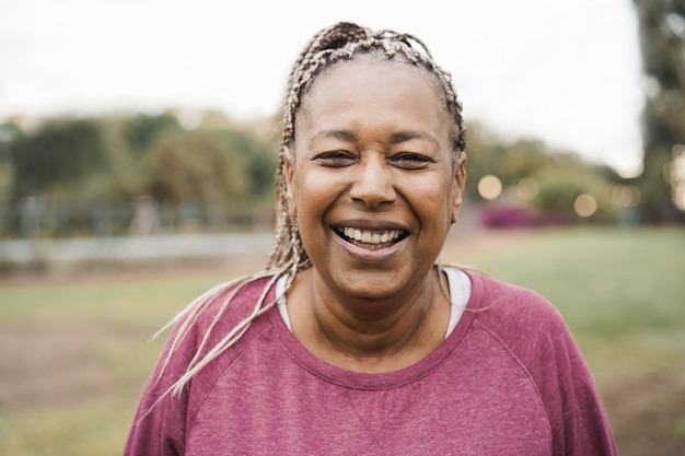 Afrikanische ältere frau, die vor der kamera draußen im stadtpark lächelt