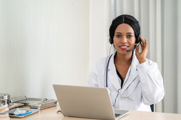Afrikanische ärztin im headset nimmt anruf auf ihr headset-mikrofon online für eine schmerzpatientin