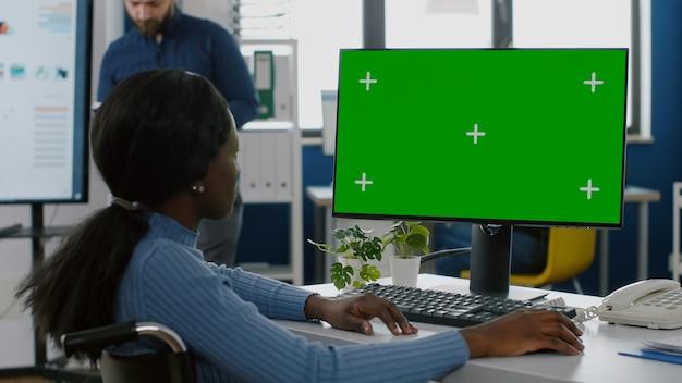 Afrikanische behinderte geschäftsfrau, die chroma-key-desktop betrachtet