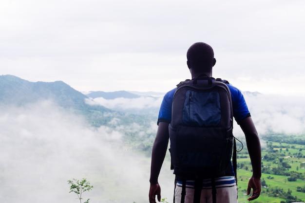 Afrikanische bergsteiger des erfolgs, die auf die oberseite des hügels schauen, bedeckten mit nebel und regen.