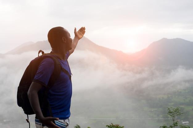 Afrikanische bergsteiger, die an der spitze des hügels bedeckt mit nebel sitzen.