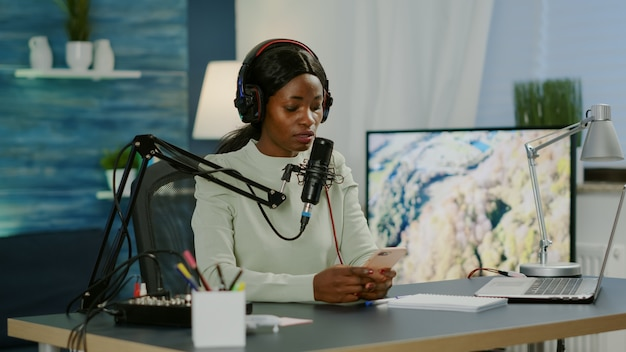Afrikanische bloggerin liest nachrichten auf dem smartphone, das videos für ihren blog im heimstudio aufzeichnet. on-air-online-produktion, internet-broadcast-show, host-streaming von live-inhalten für soziale medien