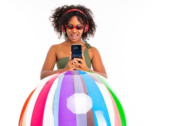 Afrikanische dame in sonnenbrille und badeanzug hält das telefon in den händen und hört musik
