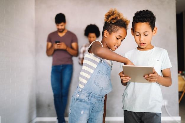 Afrikanische familie, die ihre datenschutzdaten teilt, indem sie digitale geräte, telefone, tablets verwendet