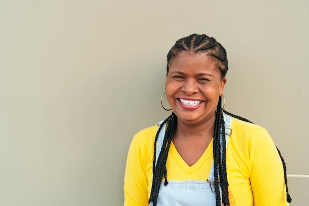 Afrikanische frau außerhalb der stadt, lächelnd in die kamera schaut.