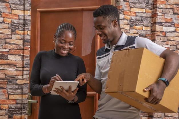 Afrikanische frau, die einen zustellnachweis unterschreibt, während sie ein paket vom kurier erhält