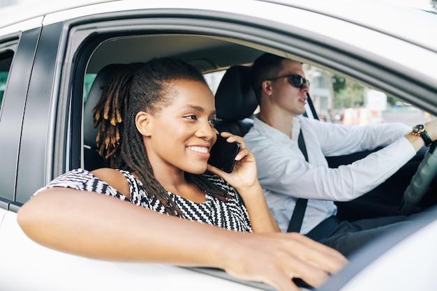 Afrikanische frau, die im auto am telefon spricht