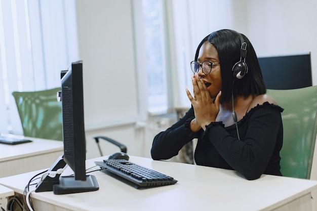 Afrikanische frau, die im informatikunterricht sitzt. dame mit brille. studentin sitzt am computer.