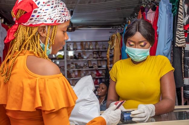 Afrikanische frau, die mit ihrer kreditkarte bezahlt, nach dem coronavirus