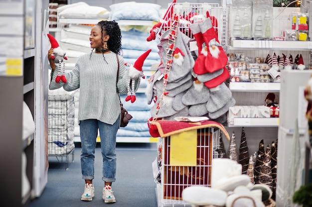 Afrikanische frau, die neujahrssachen für ihre wohnung in einem modernen einrichtungsgeschäft wählt. weihnachtsmotiv einkaufen.
