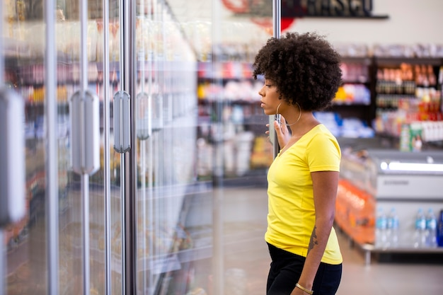 Afrikanische frau, die produkt im supermarktkühlschrank aufnimmt.