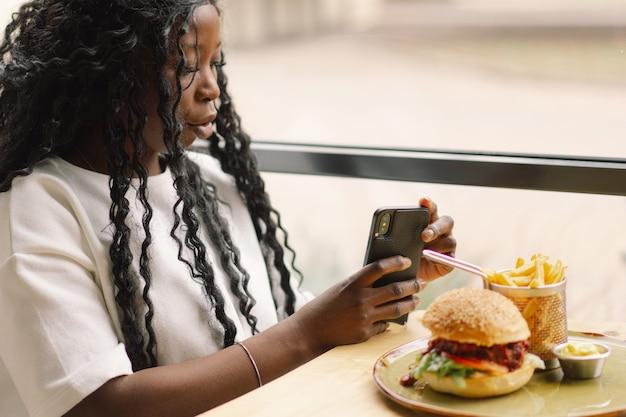 Afrikanische frau, die telefon im café benutzt