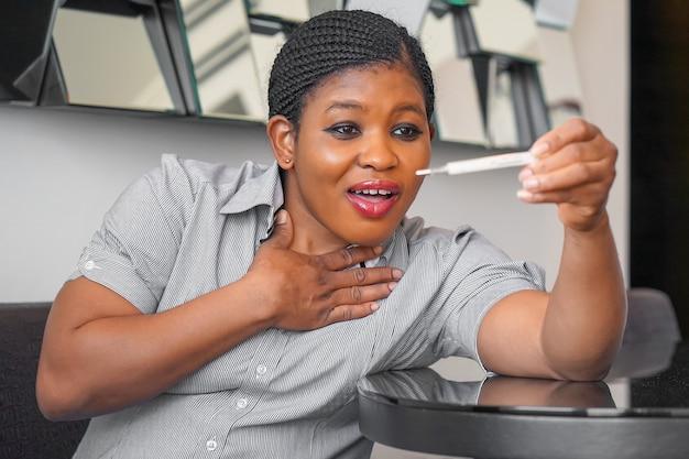 Afrikanische frau, die thermometer in händen hält, körpertemperatur misst, während an influenza leidet