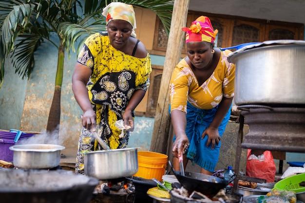 Afrikanische frau, die traditionelles essen auf der straße kocht