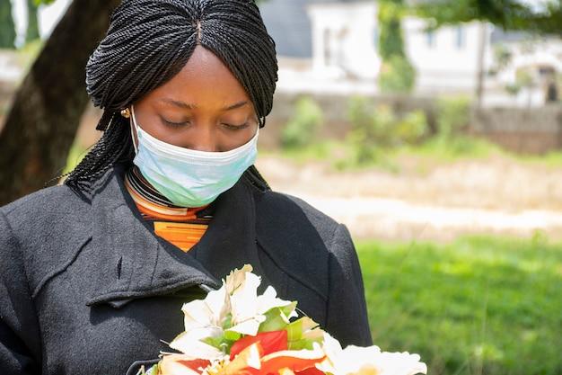 Afrikanische frau, die trauert, schwarz trägt und blumen hält
