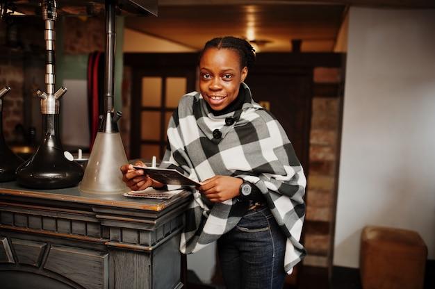 Afrikanische frau im karierten umhang posierte im shisha-café mit menü an händen.