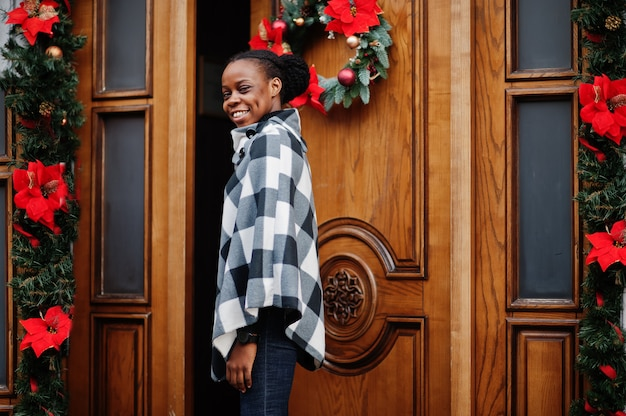 Afrikanische frau im karierten umhang stellte draußen gegen weihnachtsdekorationen auf.