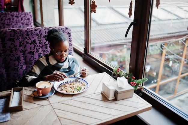 Afrikanische frau im karierten umhang und in den brillen, die am café sitzen und nachtisch essen.