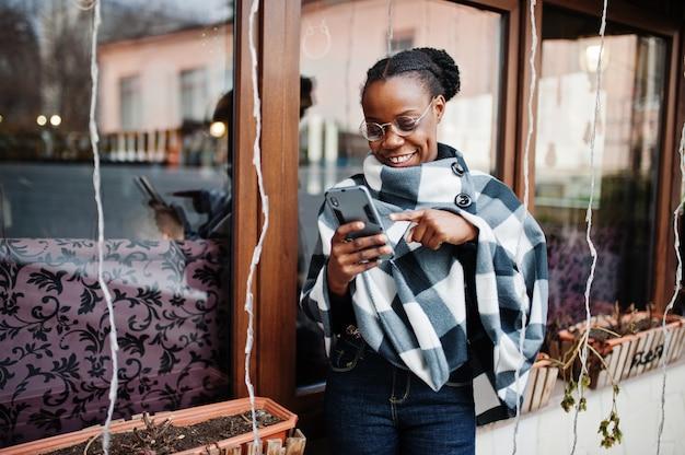 Afrikanische frau im karierten umhang und in den brillen stellte draußen auf und betrachten handy.