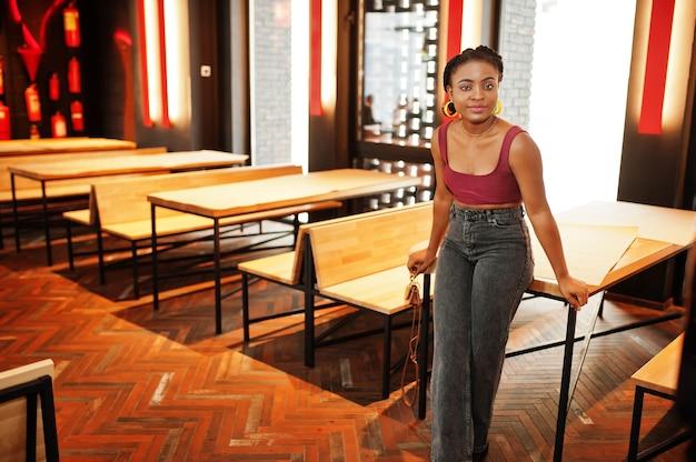 Afrikanische frau im roten marsala-oberteil und in den jeans stellte sich innen auf.