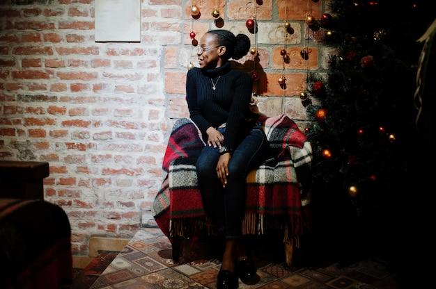Afrikanische frau im schwarzen pullover gegen neujahrsbaum mit weihnachtsdekorationen.