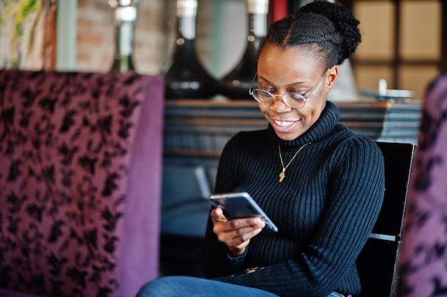 Afrikanische frau im schwarzen pullover sitzt im café und schaut auf handy.