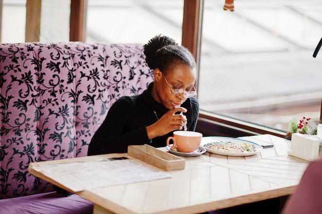 Afrikanische frau im schwarzen pullover und in den brillen stellte im café auf, sitzend am tisch mit nachtisch und tasse kaffee.