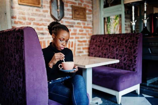 Afrikanische frau im schwarzen pullover und in den brillen stellte im café mit tasse heißem getränk auf.