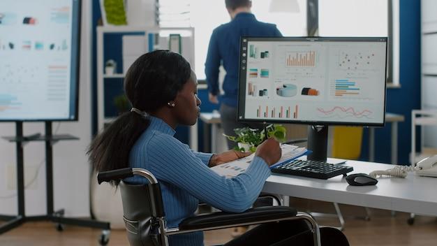 Afrikanische frau mit behinderungen immobilisiert im rollstuhl, die an der überprüfung von berichten am computer arbeitet...