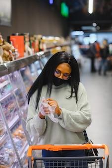 Afrikanische frau mit medizinischer einwegmaske. einkaufen im supermarkt während des ausbruchs der coronavirus-pandemie. epidemiezeit.