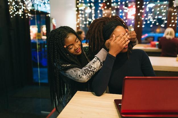 Afrikanische frau sitzen hinter ihrem freund und halten ihre augen geschlossen