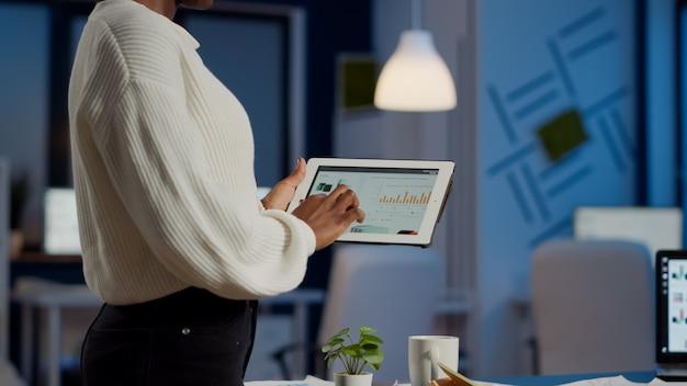 Afrikanische freiberuflerin, die ein tablet hält, das finanzdiagramme überprüft, die spät in der nacht im start-up-büro stehen. geschäftsfrau mit sozialem netzwerk, sms und blogging überstunden für den job