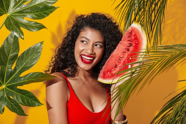 Afrikanische fröhliche positive frau in bademode, die isoliert über gelber wandwand in der nähe grüner natur tropische pflanze mit wassermelone posiert.