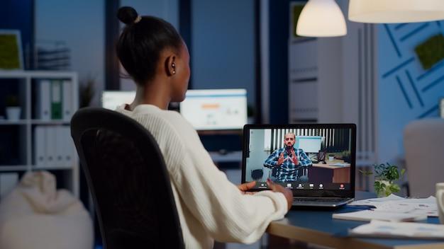 Afrikanische geschäftsfrau, die ein geschäftstreffen mit einem aus der ferne gelähmten mann mit einer webcam eines laptops hat, der in einem start-up-geschäftsbüro sitzt und überstunden macht. manager spricht um mitternacht in einer videokonferenz
