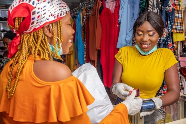 Afrikanische geschäftsfrau, die eine kreditkarte von einem kunden sammelt