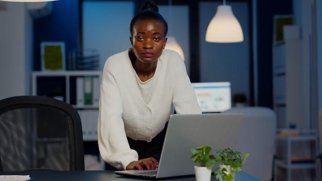 Afrikanische geschäftsfrau, die in der nähe des schreibtisches steht und in die kamera schaut, nachdem sie mails auf dem laptop gelesen hat, der spät in der nacht in einem start-up-unternehmen arbeitet. konzentrierter mitarbeiter, der das drahtlose technologienetzwerk verwendet und überstunden macht