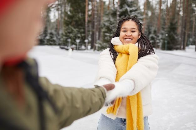 Afrikanische glückliche frau, die spaß zusammen mit ihrem freund draußen im wintertag hat