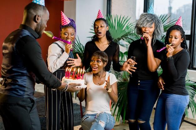 Afrikanische jugendliche mit partyhörnern und einem kuchen, der einen geburtstag feiert Premium Fotos