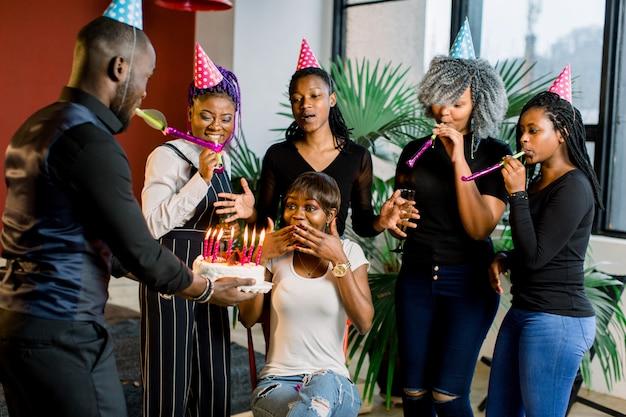 Afrikanische jugendliche mit partyhörnern und einem kuchen, der einen geburtstag feiert