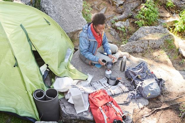 Afrikanische junge frau, die auf dem stein nahe dem zelt sitzt und heißen tee während des campings trinkt